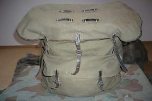 bfa4793850e Prostorný batoh měl čtyři kapsy s chlopněmi se zapínáním na kožené řemínky  s přezkami.Chlopně jsou obroubeny našitou kůží. Batoh vyráběli různé firmy  v ...